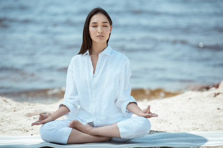Photo for focused woman meditating in ardha padmasana (half lotus pose) on yoga mat by sea - Royalty Free Image