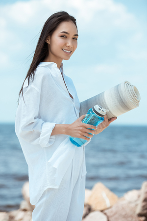Foto de smiling asian young woman holding sport bottle of water and yoga mat on beach - Imagen libre de derechos