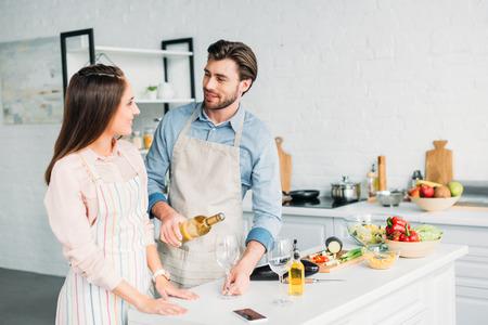 Foto de boyfriend pouring wine into glass and looking at girlfriend in kitchen - Imagen libre de derechos