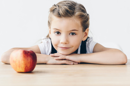 Foto de little schoolgirl sitting at table with red apple looking at camera isolated on white - Imagen libre de derechos
