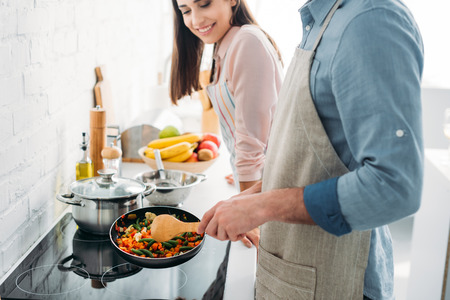 Photo pour cropped image of boyfriend frying vegetables on electric stove in kitchen - image libre de droit