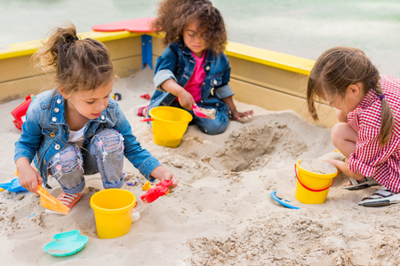 Photo pour three multiethnic little children playing with plastic scoops and buckets in sandbox at playground - image libre de droit