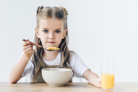 Foto de little schoolgirl eating healthy breakfast isolated on white and looking at camera - Imagen libre de derechos