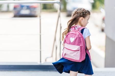 Foto de rear view of little schoolgirl with backpack on street - Imagen libre de derechos