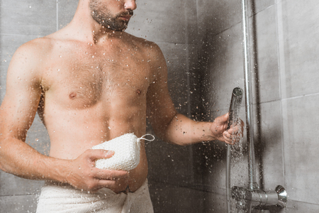 Photo pour Handsome bearded man holding sponge behind shower glass - image libre de droit