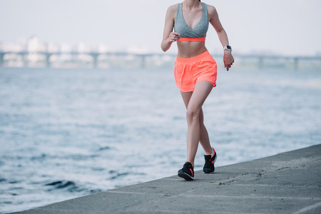 Photo for cropped view of sportswoman jogging quay near river - Royalty Free Image