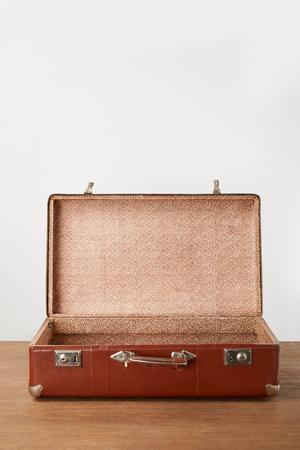 Photo pour Old open brown empty suitcase on wooden table - image libre de droit