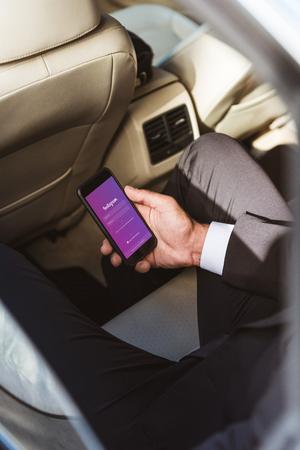 Foto de cropped image of businessman holding smartphone with loaded instagram page in car - Imagen libre de derechos