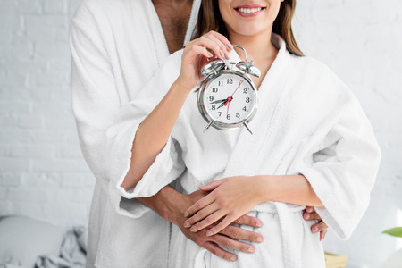 Photo pour cropped view of couple in white bathrobes holding alarm clock and standing in bedroom - image libre de droit