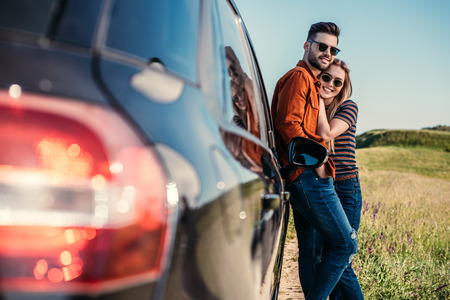 Foto de happy stylish couple in sunglasses standing near car on rural meadow - Imagen libre de derechos