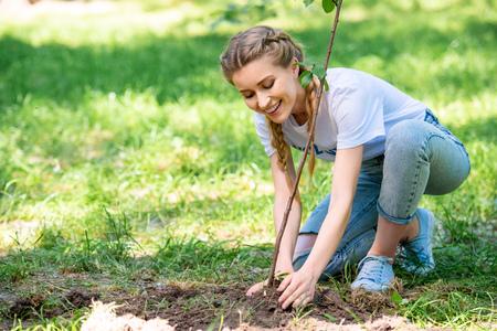 Photo pour attractive volunteer planting new tree in park - image libre de droit