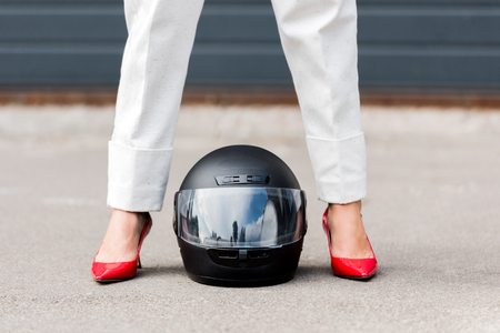 Foto de cropped image of woman in red shoes standing near motorcycle helmet on street - Imagen libre de derechos