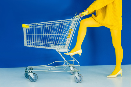 Photo for Cropped view of woman leaning on shopping cart on blue background - Royalty Free Image
