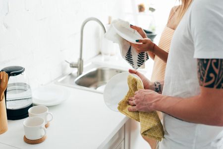 Photo pour cropped shot of man with tattooed hand and girlfriend washing dishes at kitchen - image libre de droit