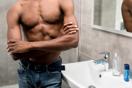Photo pour cropped shot of young african american man standing with crossed arms in bathroom - image libre de droit