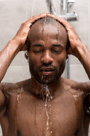 Photo for handsome young african american man washing in shower with closed eyes - Royalty Free Image