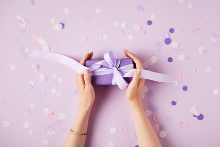 Photo for cropped image of woman holding present box at table with confetti pieces - Royalty Free Image