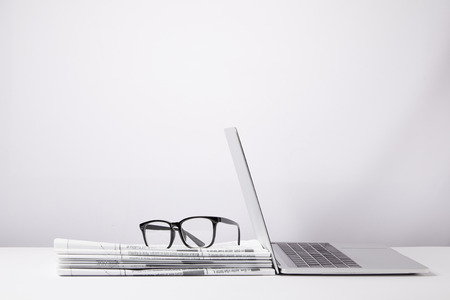 Photo for laptop and eyeglasses on heap of newspapers, on white - Royalty Free Image