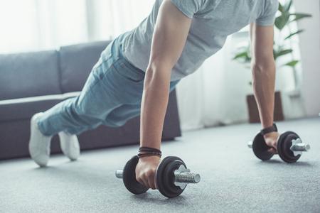 Foto de partial view of young man doing push ups with dumbbells at home - Imagen libre de derechos