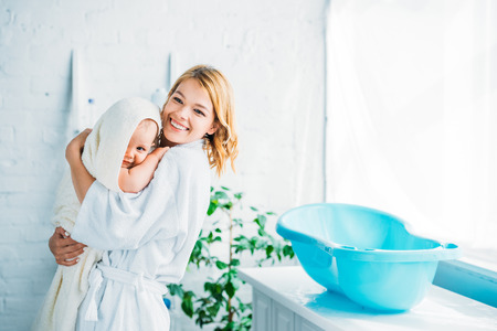 Photo pour happy mother in bathrobe carrying adorable child covered in towel near plastic baby bathtub - image libre de droit