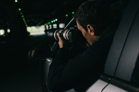 Photo for rear view of male paparazzi spying by camera with object glass from his car - Royalty Free Image