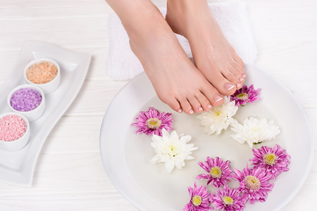 Foto de cropped shot of barefoot woman receiving bath for nails with sea salt and flowers in beauty salon - Imagen libre de derechos