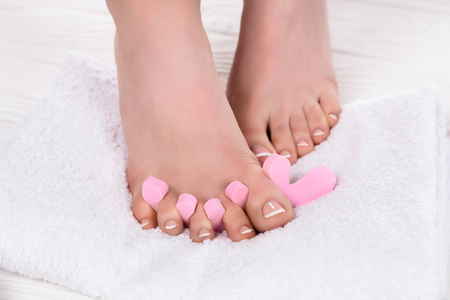 Photo pour cropped shot of barefoot woman with toe finger separator on towel in beauty salon - image libre de droit