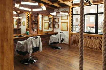 Photo for empty chairs and mirrors in modern barbershop interior - Royalty Free Image