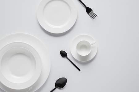 Photo for top view of various plates, cup, black spoons and fork on white table - Royalty Free Image