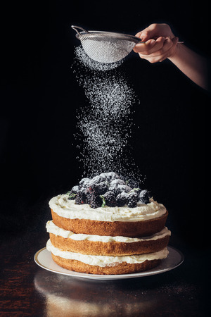 Photo for cropped shot of woman spilling sugar powder onto delicious blackberry on black - Royalty Free Image