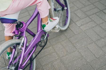 Foto de cropped shot of child riding bicycle on city street - Imagen libre de derechos