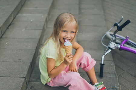 Photo pour cute child with ice cream sitting on city steps near bicycle alone - image libre de droit
