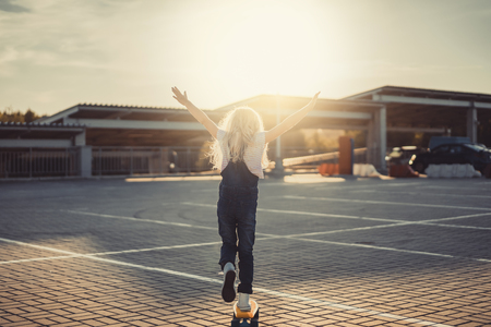 Photo pour rear view of little kid with wide arms riding on penny board at parking lot - image libre de droit