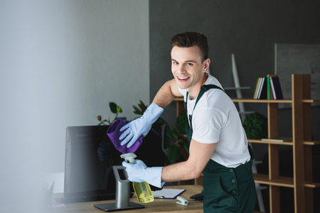 Foto de handsome young professional cleaner smiling at camera while cleaning computer monitor in office - Imagen libre de derechos