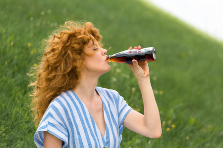 Photo pour side view of beautiful redhead woman drinking soda outdoors - image libre de droit