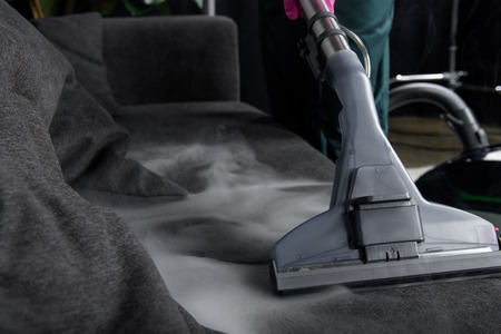Photo pour close-up view of person cleaning sofa with vacuum cleaner, hot steam cleaning concept - image libre de droit