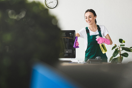 Foto de selective focus of smiling young woman with spray bottle and rag cleaning computer monitor in office - Imagen libre de derechos