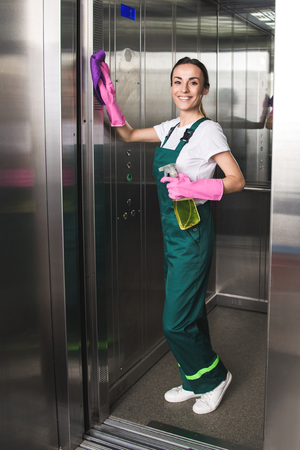 Foto de beautiful young janitor cleaning elevator and smiling at camera - Imagen libre de derechos