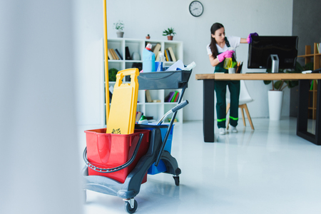Photo pour young female janitor cleaning office with various cleaning equipment - image libre de droit