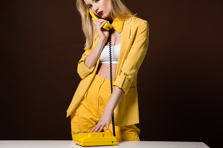 Photo for cropped shot of fashionable young woman talking by yellow vintage phone on brown - Royalty Free Image