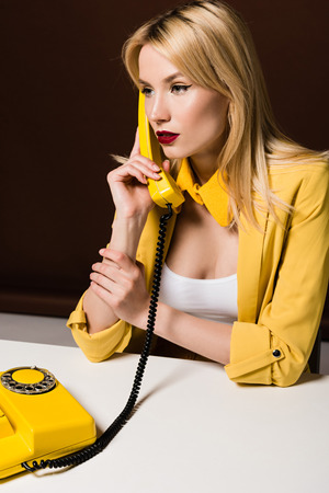Photo for stylish blonde girl in yellow clothes talking by rotary phone and looking away on brown - Royalty Free Image