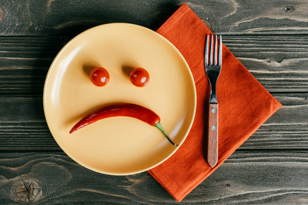 Photo for Sad smiley made of pepper and tomatoes on plate with fork on orange napkin - Royalty Free Image