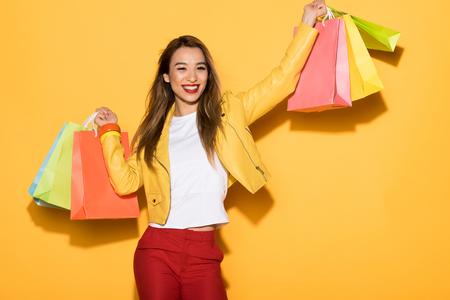 Foto für smiling asian woman with shopping bags on yellow background - Lizenzfreies Bild