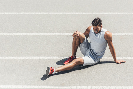 Photo pour fit young jogger with leg injury sitting on running track - image libre de droit