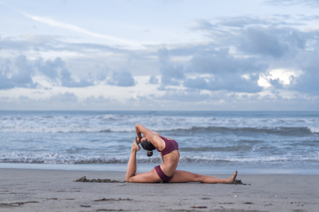 Photo for side view of young woman practicing yoga in sss pose on seashore - Royalty Free Image