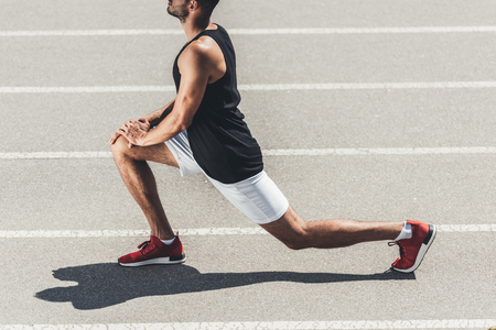 Photo pour cropped image of male jogger stretching on running track at sport playground - image libre de droit