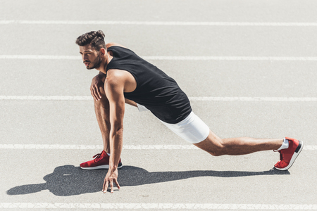 Photo pour male jogger stretching on running track at sport playground - image libre de droit