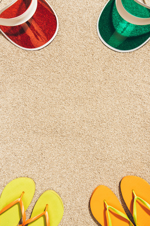 Photo for top view of arranged colorful caps and flip flops on sand - Royalty Free Image
