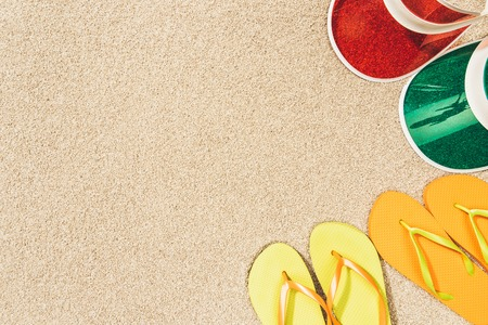 Photo for flat lay with colorful flip flops and caps arranged on sand - Royalty Free Image