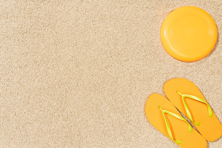 Photo for top view of yellow flip flops and frisbee on sand - Royalty Free Image
